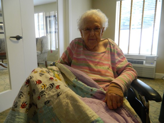 110 year-old Sina Hayes takes a break after eating breakfast in the meeting room at Brookridge Retirement Community in Winston-Salem, N.C. She displays one of her favorite quilts she has made over the years.Credit Keri Brown